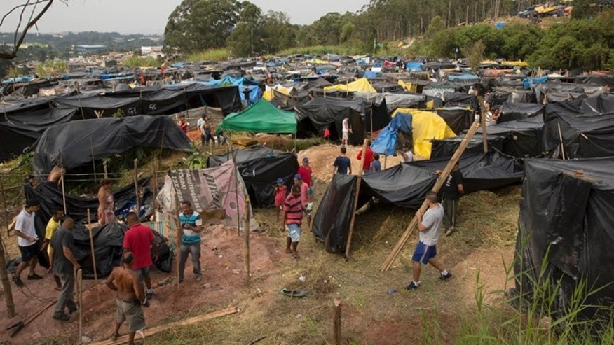 Members of the Homeless Workers Movement build their shacks within view of Itaquerao stadium in Sao Paulo, Brazil.
