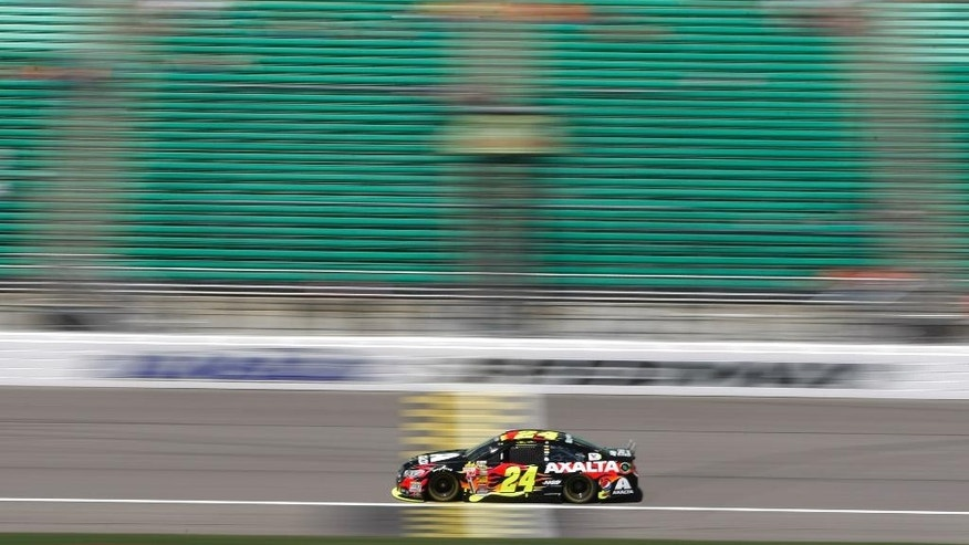 In this image taken with a slow shutter speed, driver Jeff Gordon (24) takes a practice lap Friday, May 9, 2014, at Kansas Speedway in Kansas City, Kan., for Saturday night's NASCAR Sprint Cup series auto race. (AP Photo/Colin E. Braley)