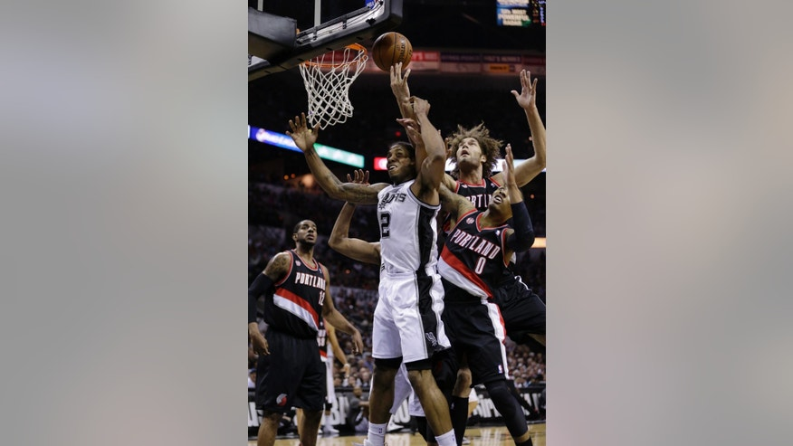 San Antonio Spurs' Kawhi Leonard (2) battles Portland Trail Blazers' Damian Lillard (0) and Robin Lopez (42) for a rebound during the first half of Game 2 of a Western Conference semifinal NBA basketball playoff series, Thursday, May 8, 2014, in San Antonio.  (AP Photo/Eric Gay)