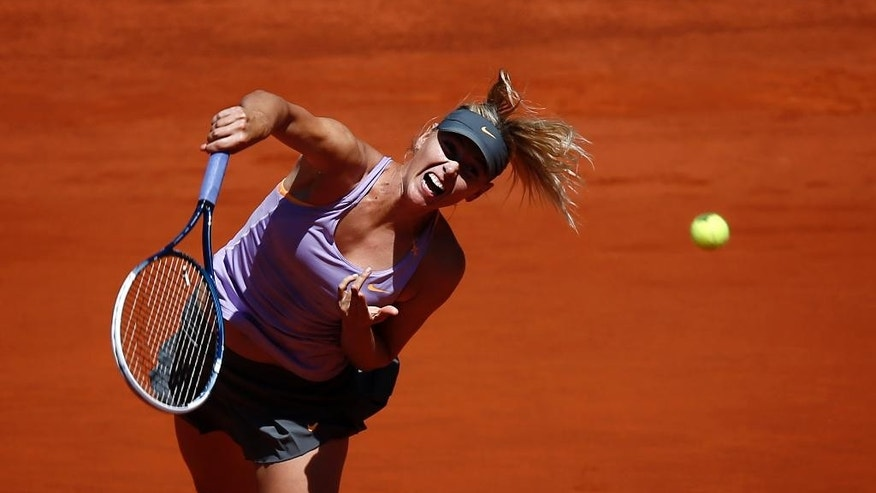 Maria Sharapova from Russia serves the ball during a Madrid Open tennis tournament match against Li Na from China in Madrid, Spain, Friday, May 9, 2014 . (AP Photo/Daniel Ochoa de Olza)