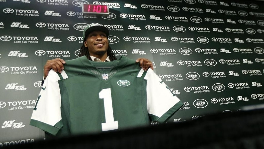 Calvin Pryor, who was drafted by the New York Jets with the 18th pick in the first round of the NFL football draft the night before, holds up a team jersey before talking to the press, Friday, May 9, 2014, in Florham Park, N.J. (AP Photo/Julio Cortez)