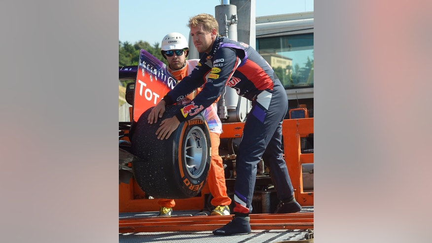 Red Bull driver Sebastian Vettel of Germany helps to put his car on a truck after he lost control  during a first free practice session at the Barcelona Catalunya racetrack in Montmelo, near Barcelona, Spain, Friday, May 9, 2014. The Formula One race will be held on Sunday. (AP Photo/Manu Fernandez)