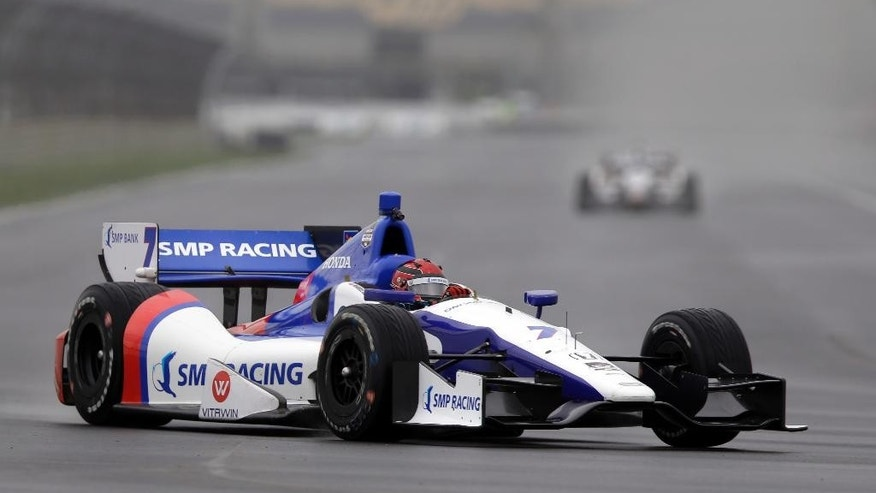 Mikhail Aleshin, of Russia, drives through turn 7 as rain falls during practice for the inaugural Grand Prix of Indianapolis IndyCar auto race at the Indianapolis Motor Speedway in Indianapolis, Friday, May 9, 2014. (AP Photo/Michael Conroy)