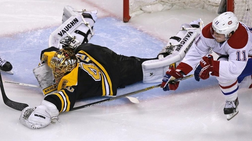 Boston Bruins goalie Tuukka Rask (40) dives out of the crease to cover the puck while pressured by Montreal Canadiens right wing Brendan Gallagher (11) during the second period of Game 5 in the second-round of the Stanley Cup hockey playoff series in Boston, Saturday, May 10, 2014. (AP Photo/Charles Krupa)