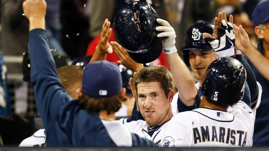 San Diego Padres' Jedd Gyorko is showered with seeds as he is greeted in the dugout following his grand slam home run against the Miami Marlins during the sixth inning of a baseball game Friday, May 9, 2014, in San Diego. It was Gyorko's second homer of the game.  (AP Photo/Lenny Ignelzi)