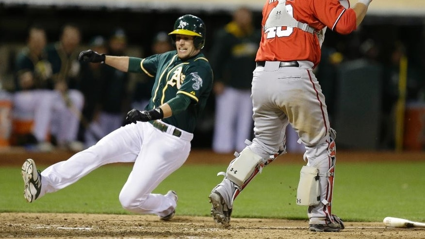 Oakland Athletics' Jed Lowrie, left, slides to score behind Washington Nationals catcher Wilson Ramos in the ninth inning of a baseball game Saturday, May 10, 2014, in Oakland, Calif. Lowrie scored on a single by Athletics' Josh Donaldson. (AP Photo/Ben Margot)