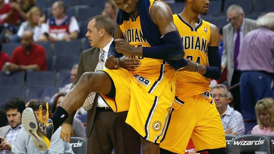 Indiana Pacers center Roy Hibbert (55) celebrates his high scoring game with teammate forward Paul George, right, during the second half of Game 3 of an Eastern Conference semifinal NBA basketball playoff game in Washington, Friday, May 9, 2014. The Pacers won 85-63. (AP Photo/Alex Brandon)