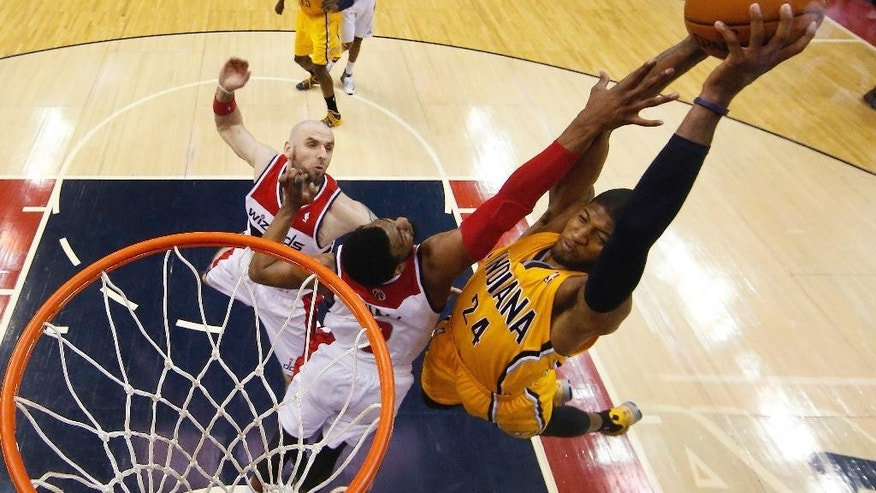 Indiana Pacers forward Paul George (24) shoots over Washington Wizards guard John Wall (2) and Washington Wizards center Marcin Gortat, left, of Poland during the second half of Game 3 of an Eastern Conference semifinal NBA basketball playoff game in Washington, Friday, May 9, 2014. The Pacers won 85-63. (AP Photo/Alex Brandon)