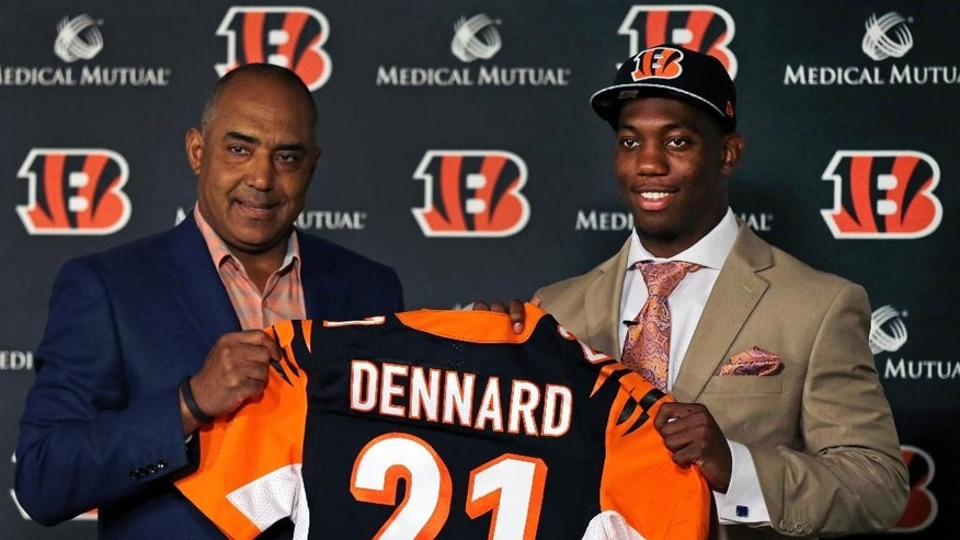 Cincinnati Bengals head coach Marvin Lewis, left, holds up a jersey with NFL football team's first round draft pick, Darqueze Dennard, a cornerback out of Michigan State, Saturday, May 10, 2014, in Cincinnati.  (AP Photo/Al Behrman)