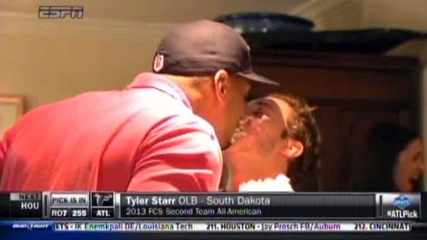 In this image taken from video, Missouri defensive end Michael Sam, left, gets a kiss at a draft party in San Diego, before he was selected in the seventh round, 249th overall, by the St. Louis Rams in the NFL draft Saturday, May 10, 2014. The Southeastern Conference defensive player of the year last season came out as gay in media interviews this year. (AP Photo/ESPN)