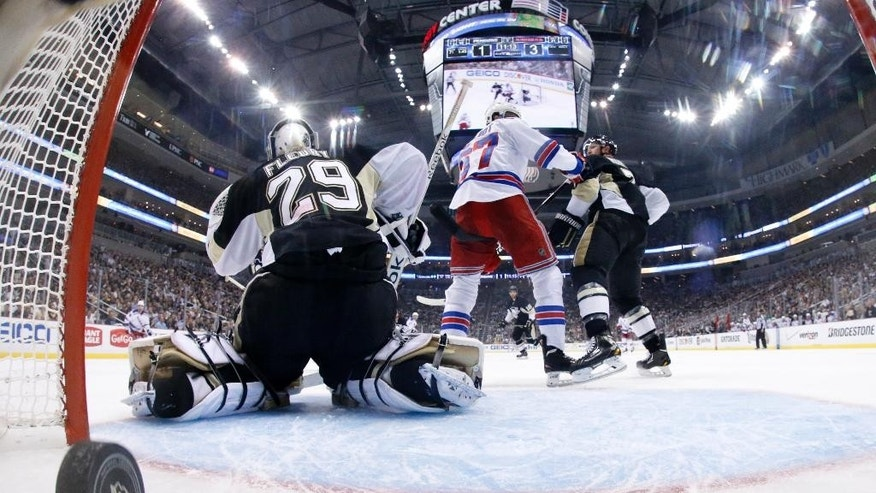 In this photo taken with a fisheye lens, a goal by New York Rangers' Ryan McDonagh (not shown) gets past Pittsburgh Penguins goalie Marc-Andre Fleury (29) in the second period of Game 5 of a second-round NHL playoff hockey series in Pittsburgh Friday, May 9, 2014. The Rangers won 5-1. (AP Photo/Gene J. Puskar)