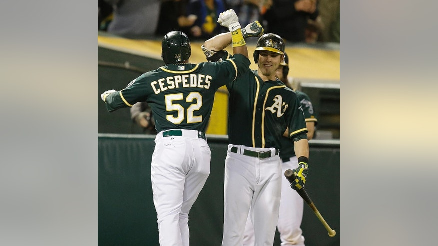 Oakland Athletics' Yoenis Cespedes (52) is congratulated by Josh Reddick, right, after Cespedes hit a home run off Washington Nationals' Doug Fister in the fifth inning of a baseball game on Friday, May 9, 2014, in Oakland, Calif. (AP Photo/Ben Margot)