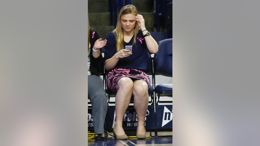 In this Wednesday, Feb. 26, 2014 photo, Natalie Lewis, right, University of Richmond director of basketball operations, looks at her phone as she sits on the bench during a game against Virginia Commonwealth University in the Robins Center in Richmond, Va. A family spokeswoman says Lewis was one of two passengers on a hot air balloon that crashed in Caroline County, Va., on May 9, 2014. (AP Photo/Richmond Times-Dispatch, Alexa Welch Edlund)