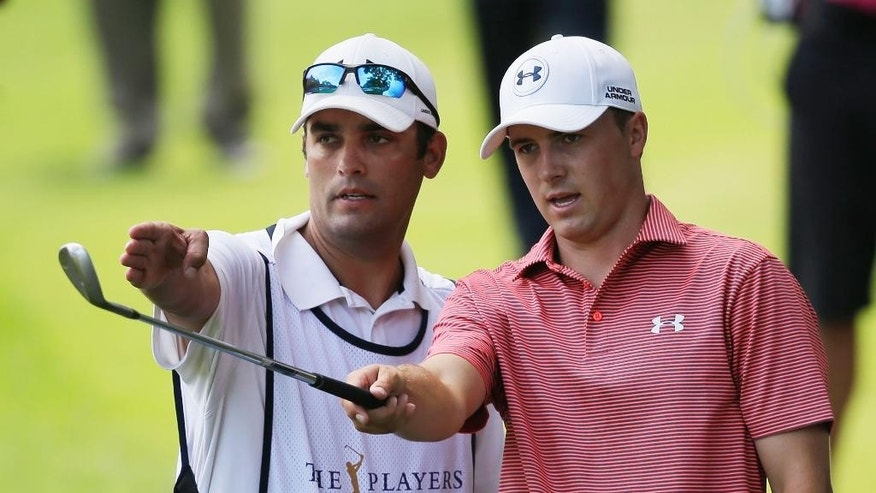 Jordan Spieth, left,  and his caddie Michael Greller gesture from the eighth fairway during the final round of The Players championship golf tournament at TPC Sawgrass, Sunday, May 11, 2014 in Ponte Vedra Beach, Fla. (AP Photo/Gerald Herbert)