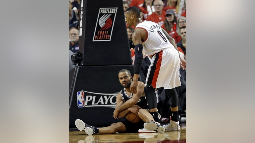 San Antonio Spurs' Tony Parker, left, calls a time out as Portland Trail Blazers' Damian Lillard (0) looks on in the second quarter of Game 3 of a Western Conference semifinal NBA basketball playoff series Saturday, May 10, 2014, in Portland, Ore. (AP Photo/Rick Bowmer)