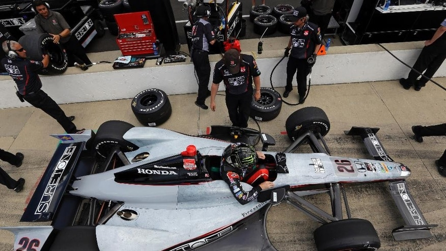Kurt Busch climbs out of his car after running laps during practice for Indianapolis 500 IndyCar auto race at the Indianapolis Motor Speedway in Indianapolis, Sunday, May 11, 2014. (AP Photo/Michael Conroy)