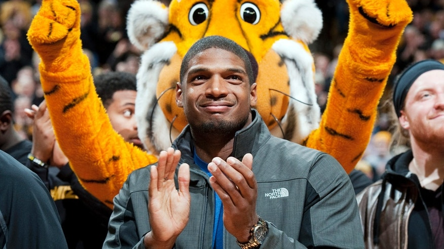 Feb. 15, 2014: In this file photo, Missouri's All-American defensive end Michael Sam claps during the Cotton Bowl trophy presentation at halftime of an NCAA college basketball game between Missouri and Tennessee in Columbia, Mo.