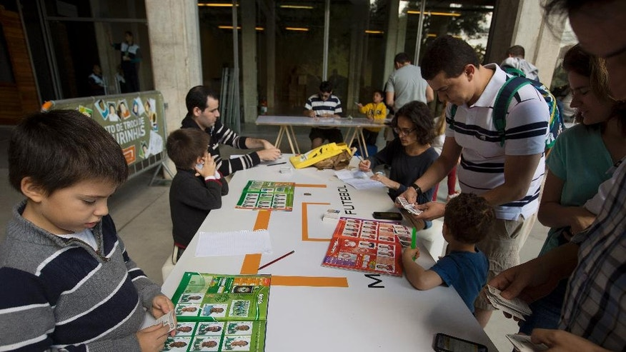 Collecters exchange World Cup stickers for their albums at a trading table outside the Pacaembu stadium in Sao Paulo, Brazil, Saturday, May 10, 2014. The frenzy over the World Cup sticker album has taken over Brazil like never before. Brazilians have long been avid fans of World Cup albums, but this year there's added motivation with the soccer tournament coming to their backyard. (AP Photo/Andre Penner)
