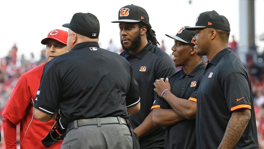 Cincinnati Bengals players, center left to right: Third round pick Will Clarke, a defensive end from West Virginia; first round pick Darqueze Dennard, a cornerback from Michigan State; and second round pick Jeremy Hill, a running back from LSU, stand at home plate as they help Cincinnati Reds manager Bryan Price, left, bring out the lineup card prior to a baseball game against the Colorado Rockies, Saturday, May 10, 2014, in Cincinnati. (AP Photo/Al Behrman)