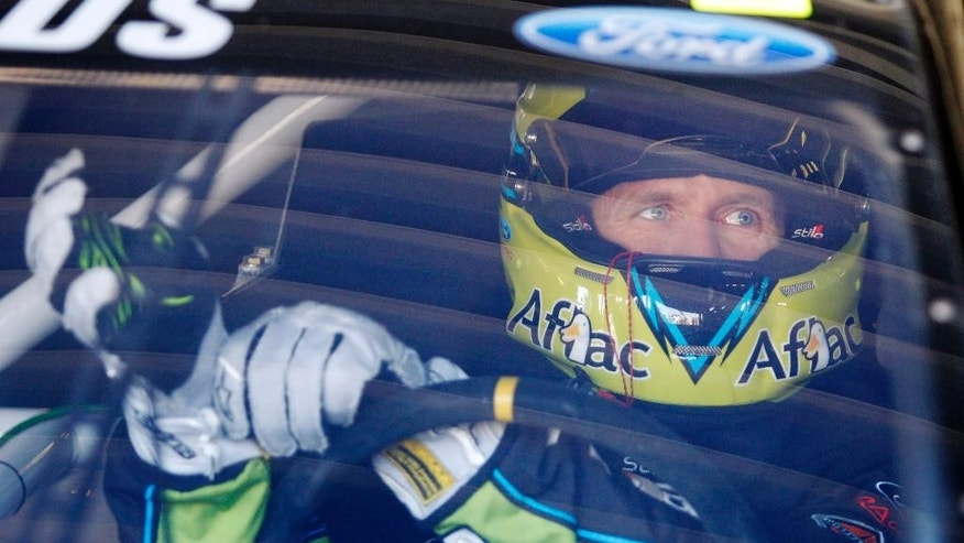 Driver Carl Edwards adjusts his gloves before practice, Friday, May 9, 2014, at Kansas Speedway in Kansas City, Kan., for Saturday night's NASCAR Sprint Cup series auto race. (AP Photo/Colin E. Braley)