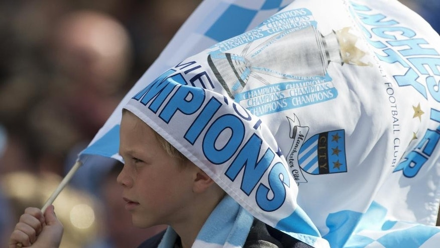 A young Manchester City supporter holds a flag before the soccer team pass by in a street parade in the city centre, the day after their team won the English Premier League title, in Manchester, England, Monday May 12, 2014. (AP Photo/Jon Super)