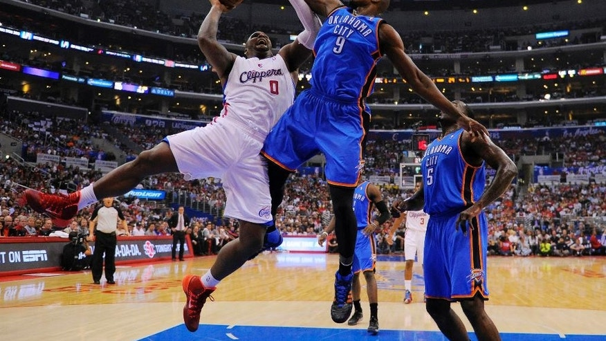Los Angeles Clippers forward Glen Davis, left, shoots as Oklahoma City Thunder forward Serge Ibaka, center, and center Kendrick Perkins defend in the first half of Game 4 of the Western Conference semifinal NBA basketball playoff series on Sunday, May 11, 2014, in Los Angeles. (AP Photo/Mark J. Terrill)