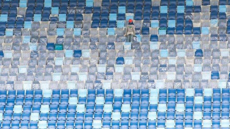 This April 22, 2014 photo released by Portal da Copa, shows a worker walk in the stands at the Arena Pantanal in Cuiaba, Brazil. Brazil had seven years to get ready for the World Cup, but it enters the final month of preparations with a lot yet to be done. There is also concern with the temporary structures at the Beira-Rio Stadium in southern Porto Alegre, and the other incomplete venue is the Arena Pantanal in the western city of Cuiaba, which is only expected to host an official test event at the end of the month. (AP Photo/Jose Medeiros-Portal da Copa)