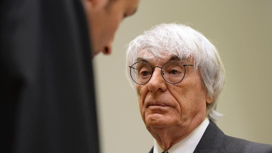 "Formula One boss Bernie Ecclestone, right, waits prior to the fourth day of his trial at the courthouse in Munich, southern Germany, Tuesday, May 13, 2014. Ecclestone is charged with bribery and incitement to breach of trust ""in an especially grave case"" over a US dollar 44 million payment to a German banker, that prosecutors allege was meant to facilitate the sale of the Formula One Group to a buyer of Ecclestone's liking. (AP Photo/Christof Stache, Pool)"