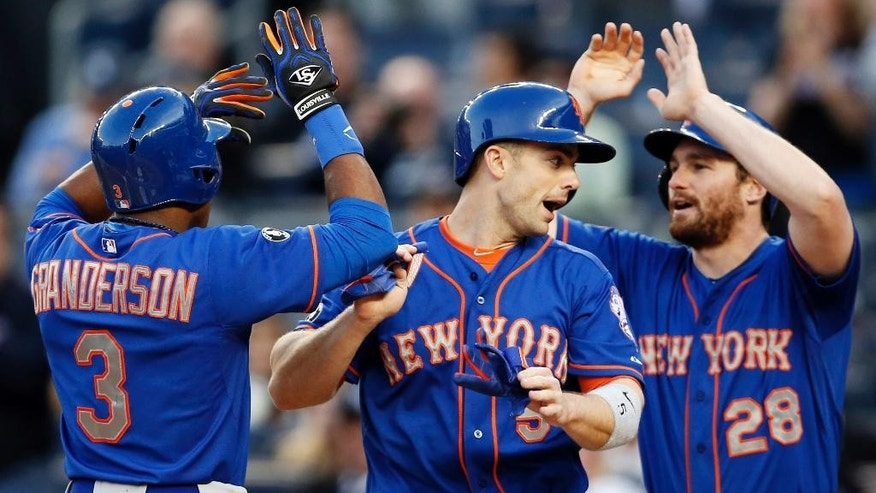 New York Mets Curtis Granderson celebrates with David Wright, center, and Daniel Murphy after Granderson hit a first-inning, three-run, home run in a baseball game at Yankee Stadium in New York, Tuesday, May 13, 2014.  (AP Photo)