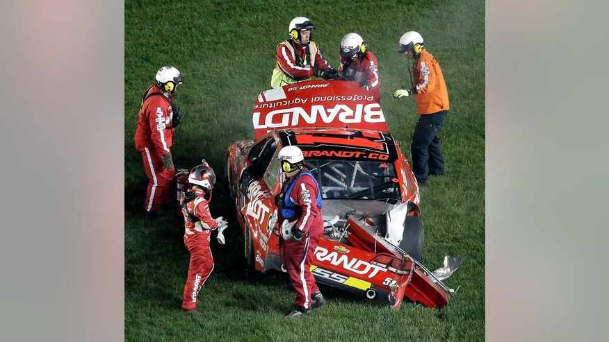 Justin Allgaier is helped out of his car after crashing during a NASCAR Sprint Cup Series auto race at Kansas Speedway in Kansas City, Kan., Saturday, May 10, 2014. (AP Photo/Charlie Riedel)