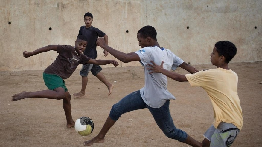 Young residents play soccer at the Sao Carlos slum in Rio de Janeiro, Brazil, Monday, May 12, 2014. As opening day for the World Cup approaches, people continue to stage protests, some about the billions of dollars spent on the World Cup at a time of social hardship, but soccer is still a unifying force. The international soccer tournament will be the first in the South American nation since 1950. (AP Photo/Felipe Dana)