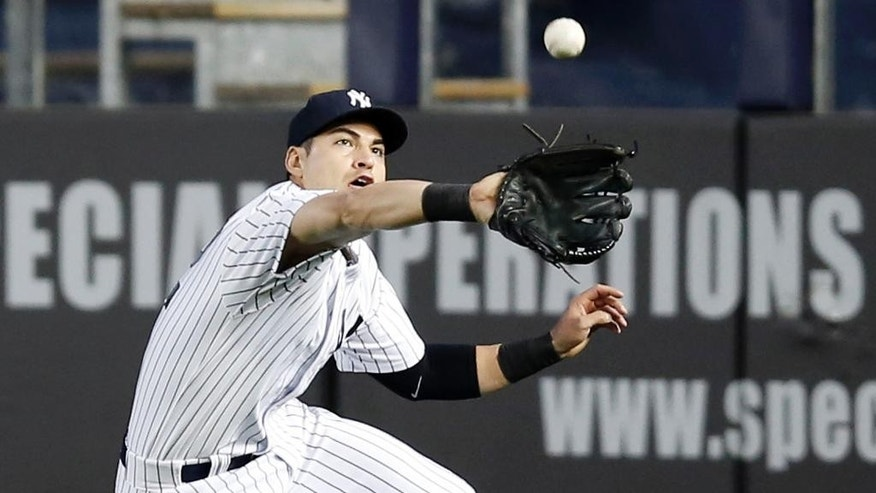 New York Yankees center fielder Jacoby Ellsbury fields a Juan Lagares third-inning sacrifice fly in a baseball game against the New York Mets at Yankee Stadium in New York, Tuesday, May 13, 2014.  (AP Photo)