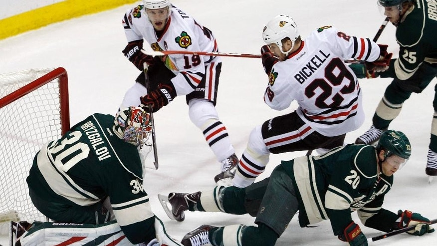 Chicago Blackhawks left wing Bryan Bickell (29) lands on Minnesota Wild defenseman Ryan Suter (20) as Wild goalie Ilya Bryzgalov (30), of Russia, deflects a shot during the first period of Game 6 of an NHL hockey second-round playoff series in St. Paul, Minn., Tuesday, May 13, 2014. (AP Photo/Ann Heisenfelt)