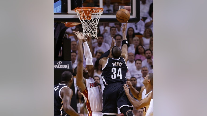 Brooklyn Nets forward Paul Pierce (34) goes to the basket as Miami Heat center Chris Bosh (1) defends during the first half of Game 5 of a second-round NBA playoff basketball game in Miami, Wednesday, May 14, 2014. (AP Photo)