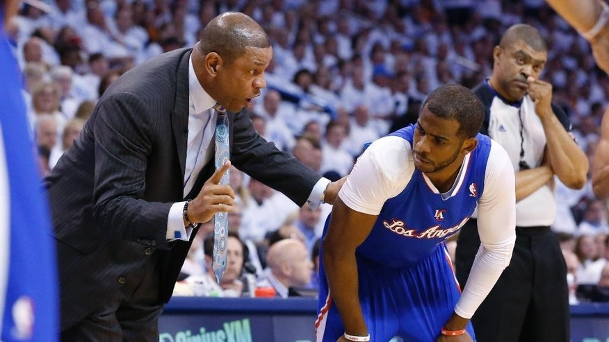 Los Angeles Clippers coach Doc Rivers, left, talks to guard Chris Paul in the first quarter of Game 5 of the Western Conference semifinal NBA basketball playoff series against the Oklahoma City Thunder, in Oklahoma City, Tuesday, May 13, 2014. (AP Photo)