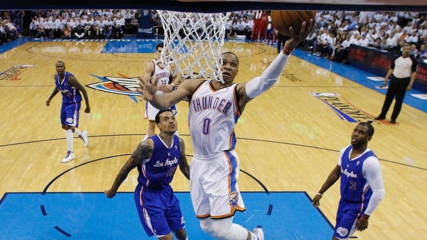 Oklahoma City Thunder guard Russell Westbrook (0) shoots between Los Angeles Clippers forward Matt Barnes (22) and guard Chris Paul (3) in the second quarter of Game 5 of the Western Conference semifinal NBA basketball playoff series, in Oklahoma City on Tuesday, May 13, 2014. (AP Photo)