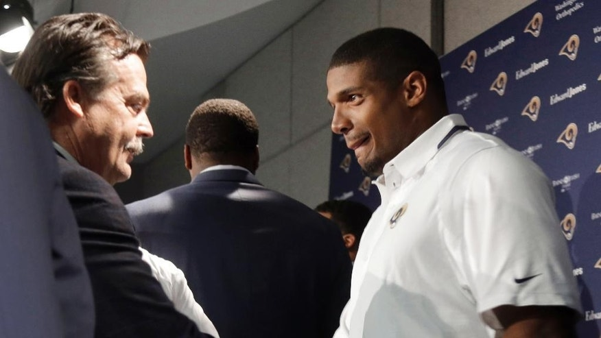 St. Louis Rams seventh-round draft pick Michael Sam, right, shakes hands with coach Jeff Fisher during a news conference at the NFL football team's practice facility Tuesday, May 13, 2014, in St. Louis. (AP Photo/Jeff Roberson)