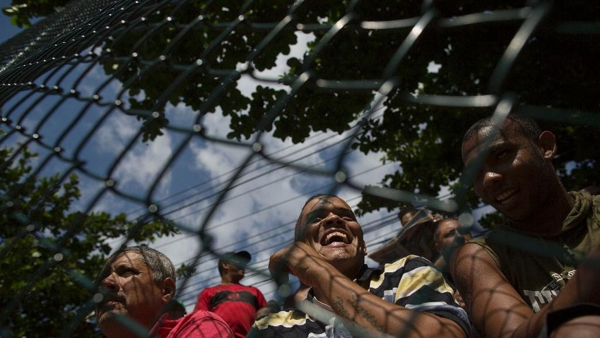 In this April 27, 2014 photo, residents watch an amateur soccer match behind a fence at the Vila da Penha neighborhood of Rio de Janeiro, Brazil. Brazil is a five-time champion of the World Cup, and will host this year's international soccer tournament starting June 12. The government says it wants to use the World Cup to convince international visitors to keep coming back to Brazil after the tournament ends. (AP Photo/Leo Correa)