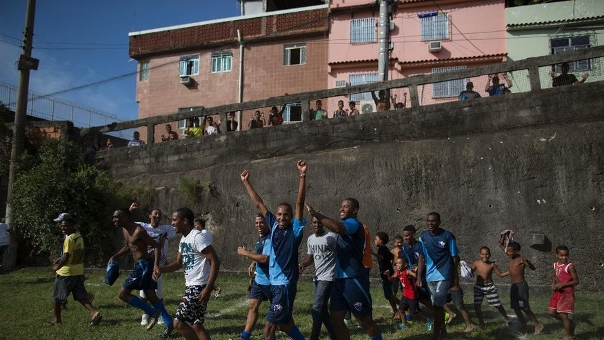 In this May 03, 2014 photo, players from the Escada Azul team celebrate classifying for the semi-finals of an amateur soccer tournament in the Mangueira shantytown of Rio de Janeiro, Brazil. The high costs of preparing for the 2013 Confederations Cup and upcoming World Cup, blamed in part by the late rush to get projects done, ignited a wave of public criticism from a population already tired of poor public services and widespread corruption and yet, in Brazil, soccer is a unifying force. (AP Photo/Leo Correa)