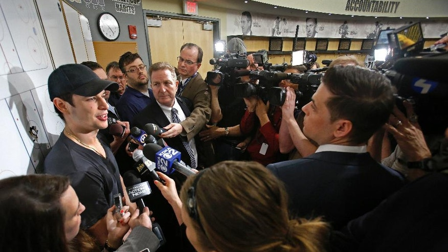 Pittsburgh Penguins captain Sidney Crosby, left, is surrounded by reporters in the Penguins' locker room during locker clean out day at the Consol Energy Center in Pittsburgh, Thursday, May 15, 2014. (AP Photo/Gene J. Puskar)