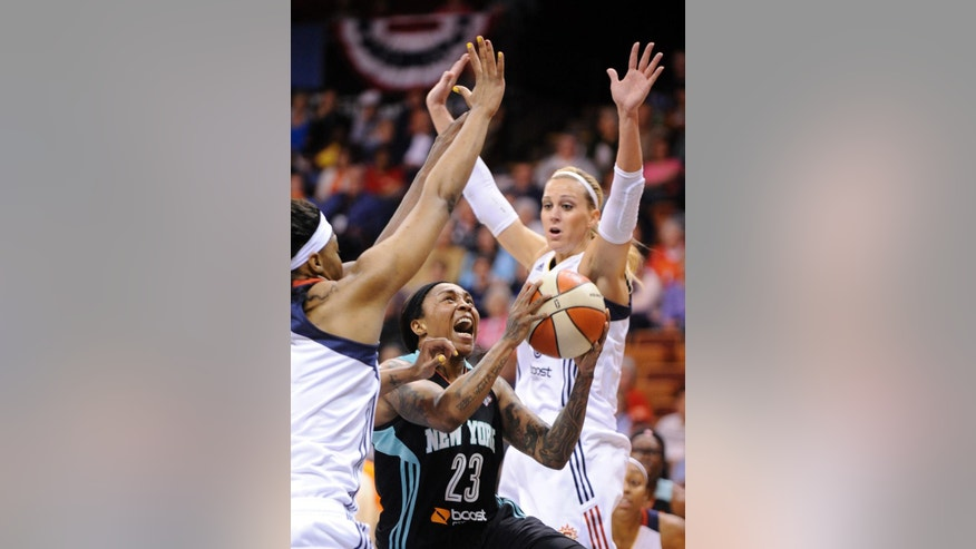 New York Liberty's Cappie Pondexter, center, drives past Connecticut Sun's Kelsey Bone, left and Katie Douglas, right,  during the first half of their WNBA basketball game in Uncasville, Conn., Friday, May 16, 2014. (AP Photo/Fred Beckham)