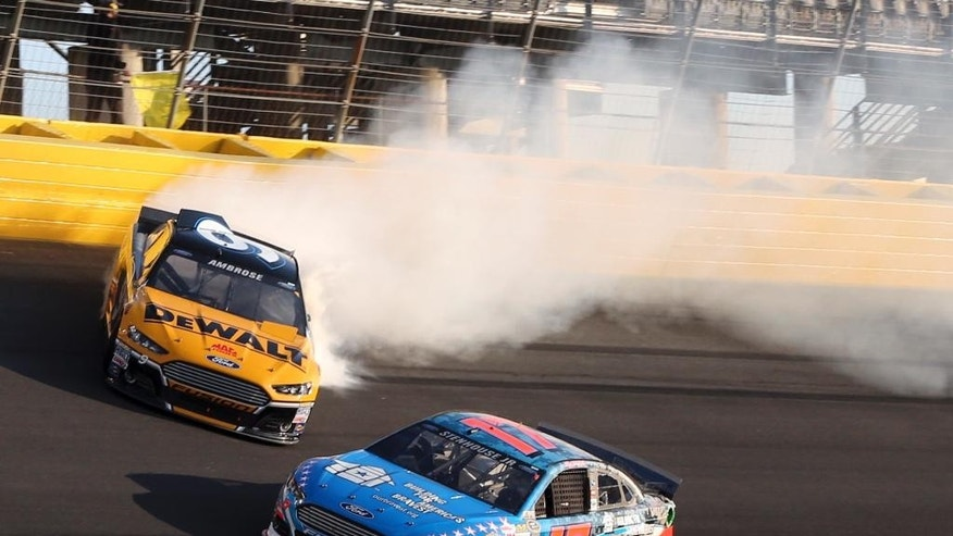 Marcus Ambrose (9) spins as Ricky Stenhouse Jr (17) drives past during the NASCAR Sprint Showdown auto race at Charlotte Motor Speedway in Concord, N.C., Friday, May 16, 2014. (AP Photo/Bob Jordan)