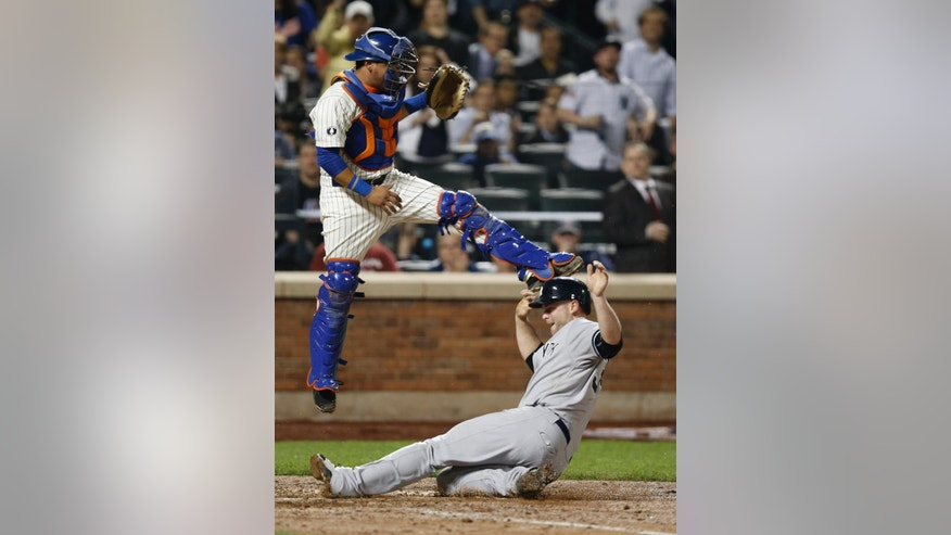 New York Yankees' Brian McCann scores on Alfonso Soriano's seventh-inning double, sliding in beneath New York Mets catcher Juan Centeno during a baseball game in New York, Thursday, May 15, 2014. (AP Photo/Kathy Willens)