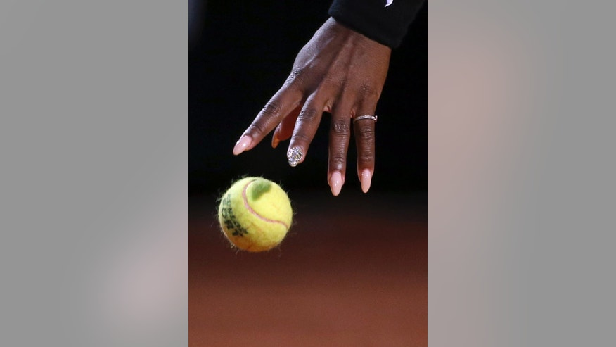 Serena Williams' hand reaches for the ball as she gets ready and serve to China's Shuai Zhang, during their match at the Italian open tennis tournament in Rome, Friday, May 16, 2014. (AP Photo/Gregorio Borgia)