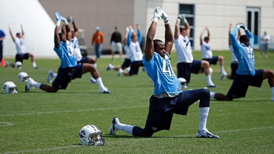 Tennessee Titans linebacker Jamal Merrell, center, stretches during NFL football rookie minicamp Friday, May 16, 2014, in Nashville, Tenn. (AP Photo/Mark Humphrey)