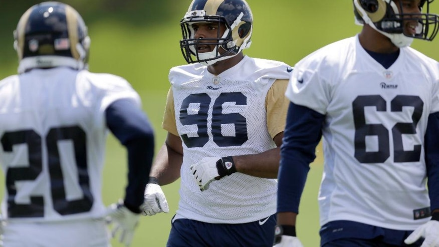 St. Louis Rams rookie defensive end Michael Sam stretches during the team's NFL football rookie camp  Friday, May 16, 2014, in St. Louis. (AP Photo/Jeff Roberson)
