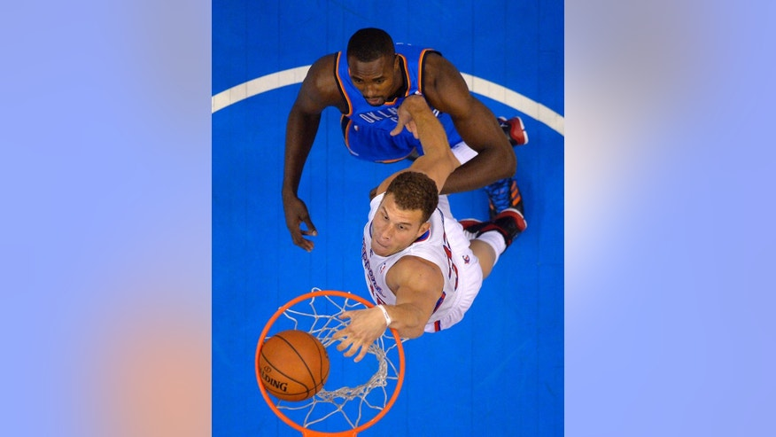 Los Angeles Clippers forward Blake Griffin, below, dunks as Oklahoma City Thunder forward Serge Ibaka, of Congo, defends in the first half of Game 6 of the Western Conference semifinal NBA basketball playoff series, Thursday, May 15, 2014, in Los Angeles. (AP Photo/Mark J. Terrill)