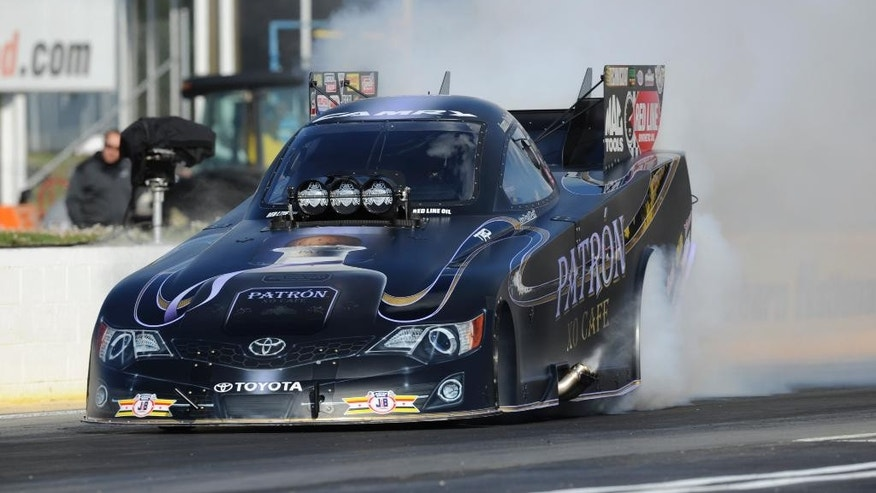 In this photo provided by the NHRA, Alexis DeJoria does a burnout during Funny Car qualifying for the NHRA Southern Nationals drag races at Atlanta Dragway on Friday, May 16, 2014, in Commerce, Ga. DeJoria took the top spot on the first day of qualifying. (AP Photo/NHRA, Marc Gewertz)