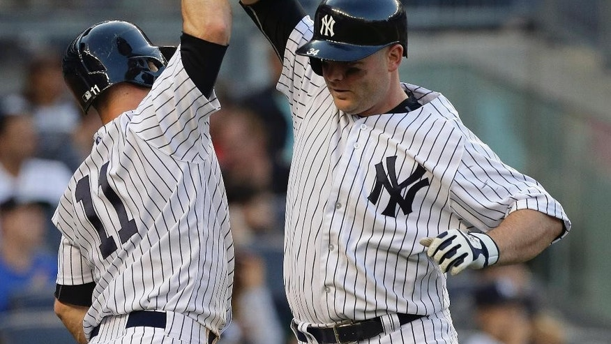 New York Yankees' Brian McCann, right, is greeted by Brett Gardner (11) after hitting a two-run home run against the Pittsburgh Pirates during the eighth inning of a baseball game, Saturday, May 17, 2014, in New York. The Yankees won 7-1. (AP Photo/Julie Jacobson)