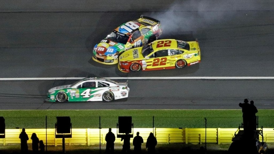 Kyle Busch (18) and Joey Logano (22) collide in Turn 3 as Kevin Harvick (4) drives low during the NASCAR Sprint All-Star auto race at Charlotte Motor Speedway in Concord, N.C., Saturday, May 17, 2014. (AP Photo/Gerry Broome)